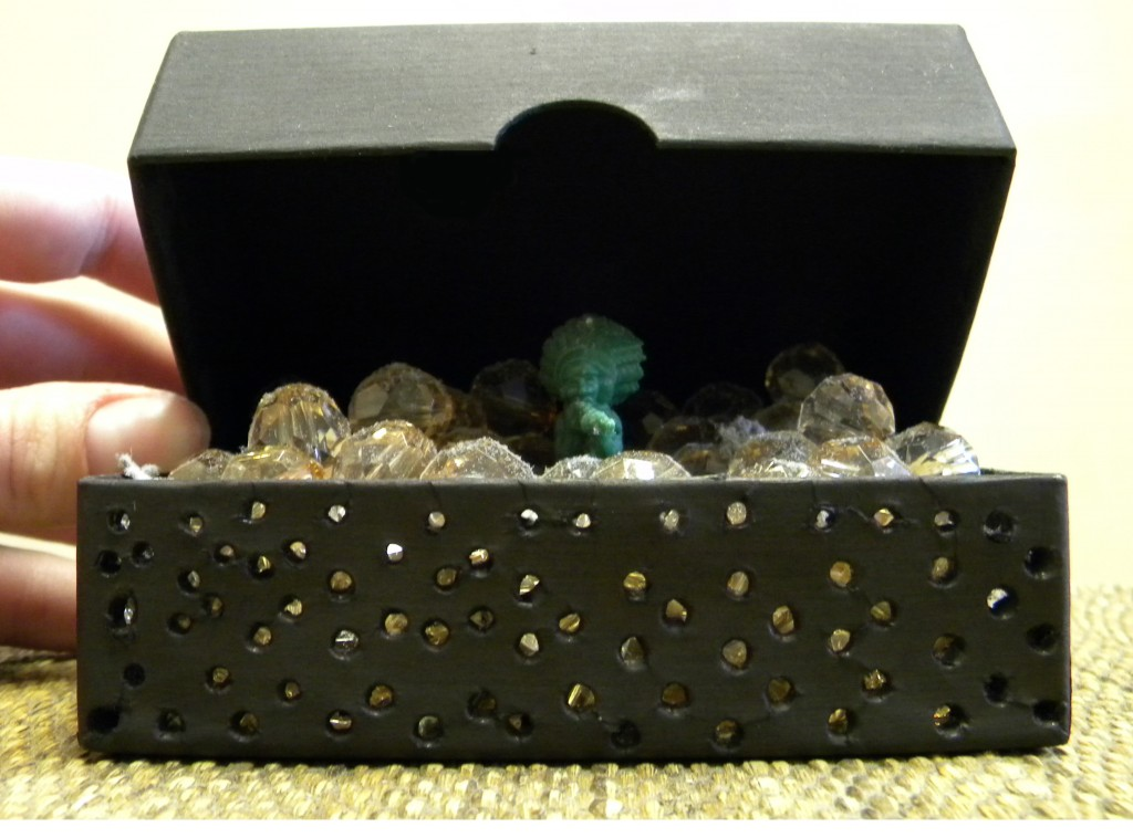 Boxed, custom for exhibition 'Boxed In and Out,' provided found box, found beads and plastic toy, collected dust; 2010